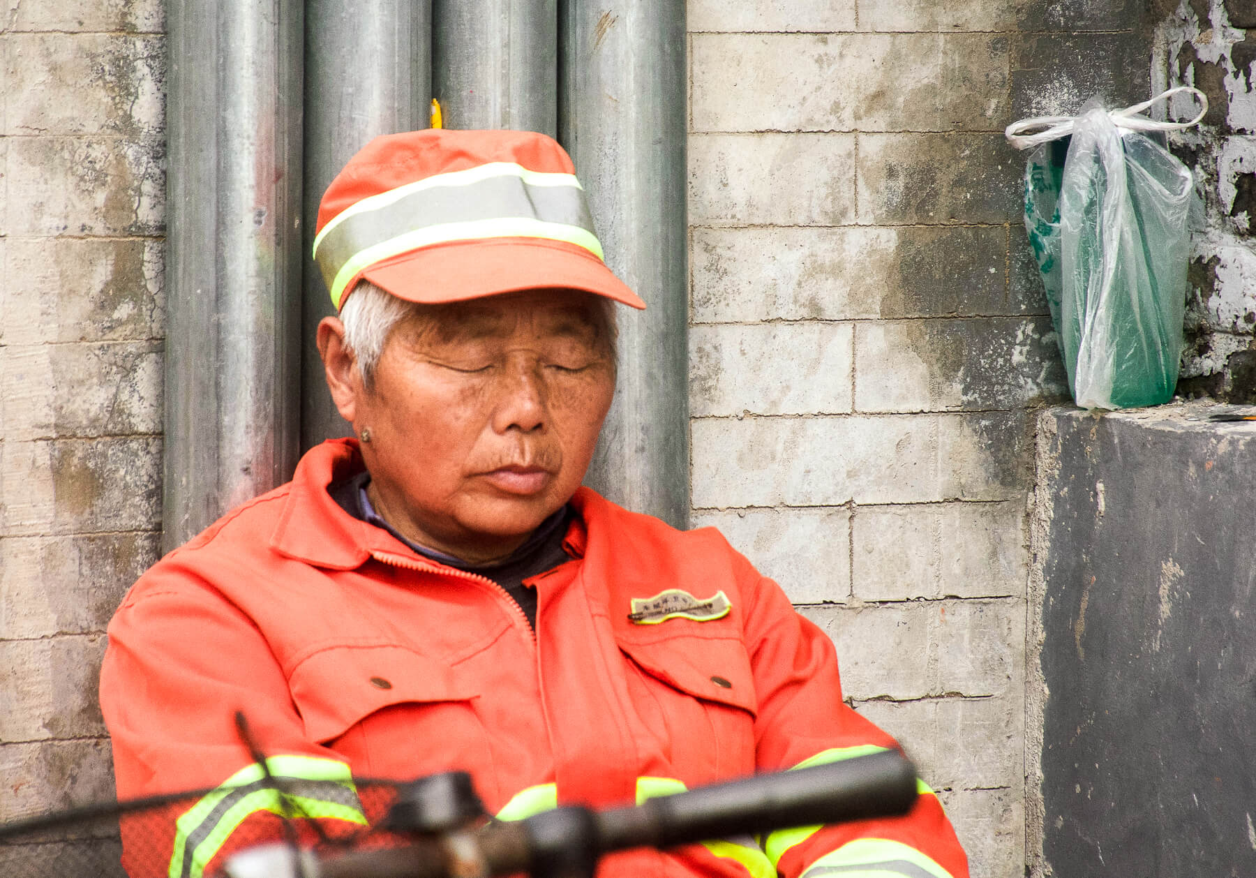 A tanned Chinese lady wearing fluorescent hi-vis gear, sleeping against a wall in Hutong, Beijing