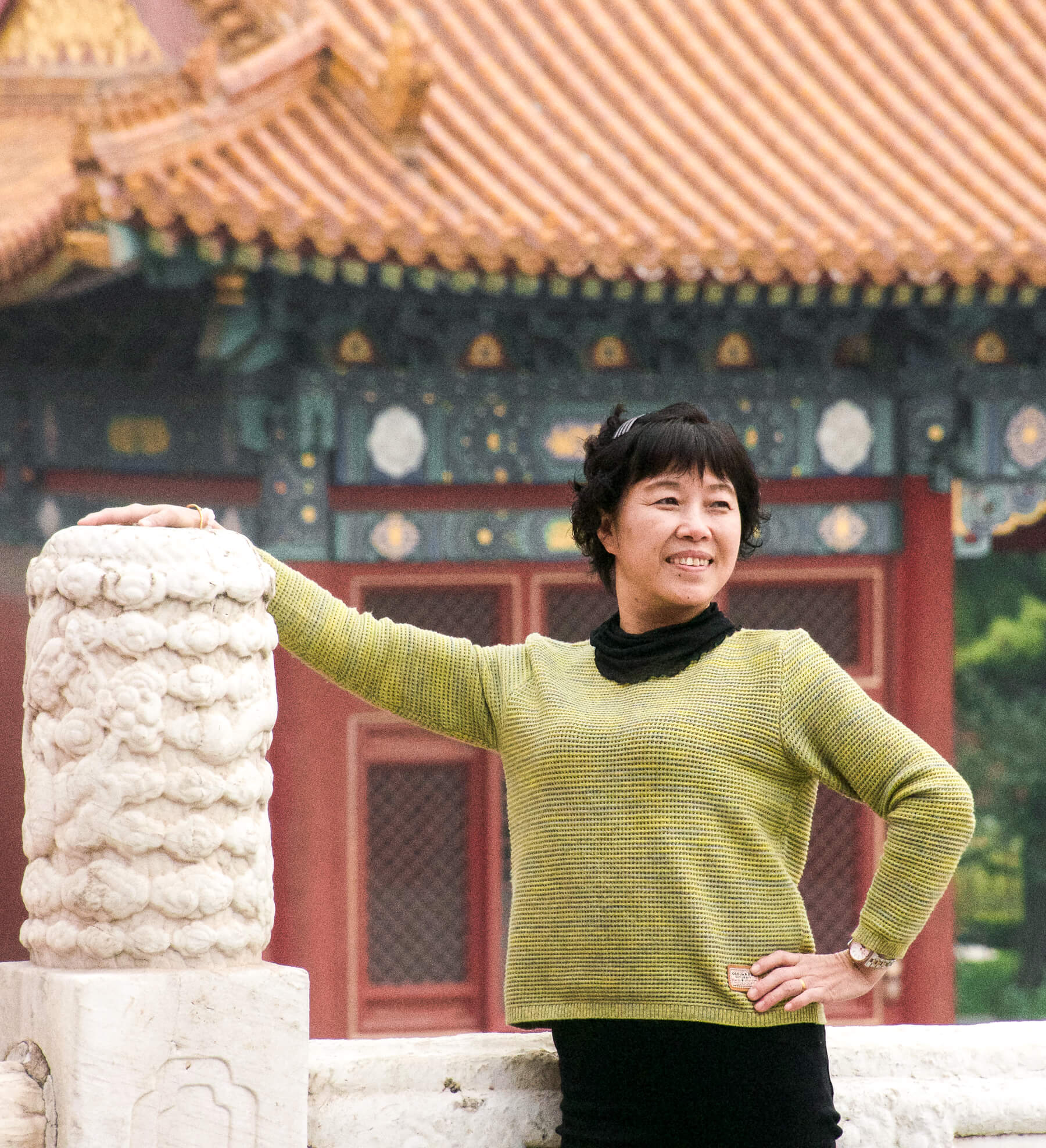 A lady posing in the Forbidden City of Beijing, holding onto a marble pillar