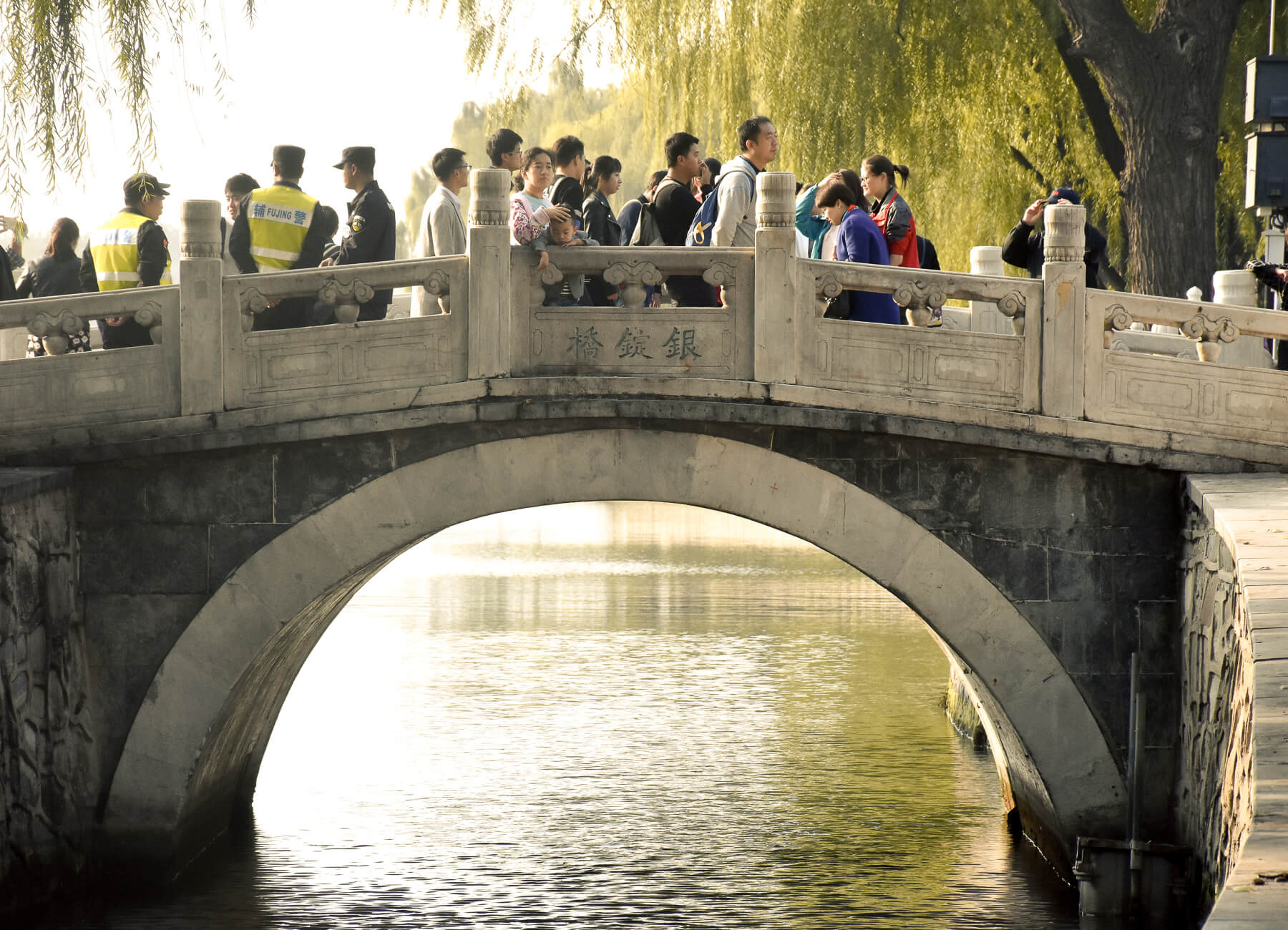 Chinese locals crossing a detailed bridge in Hutong