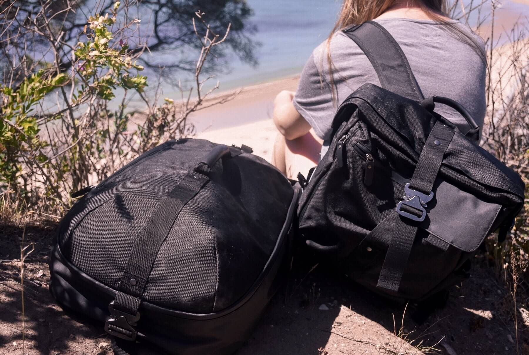 A girl overlooking the ocean with a black day bag on her back, and a big black duffle next to her