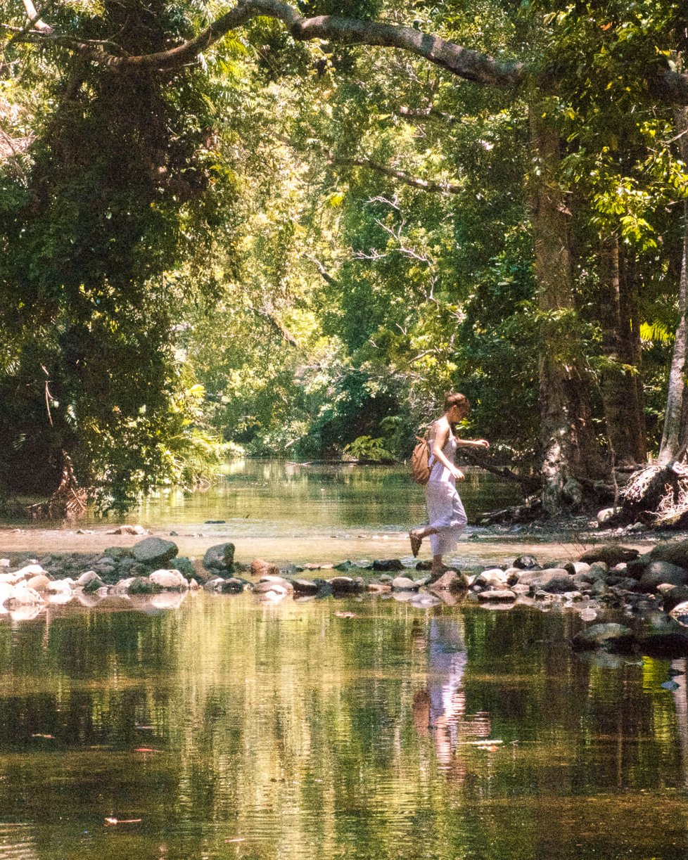Girl walking across rocks at Emmergen Creek, Cape Tribulation