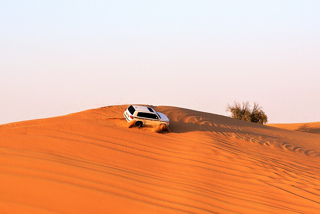 White 4WD driving along the red sand dunes in Abu Dhabi