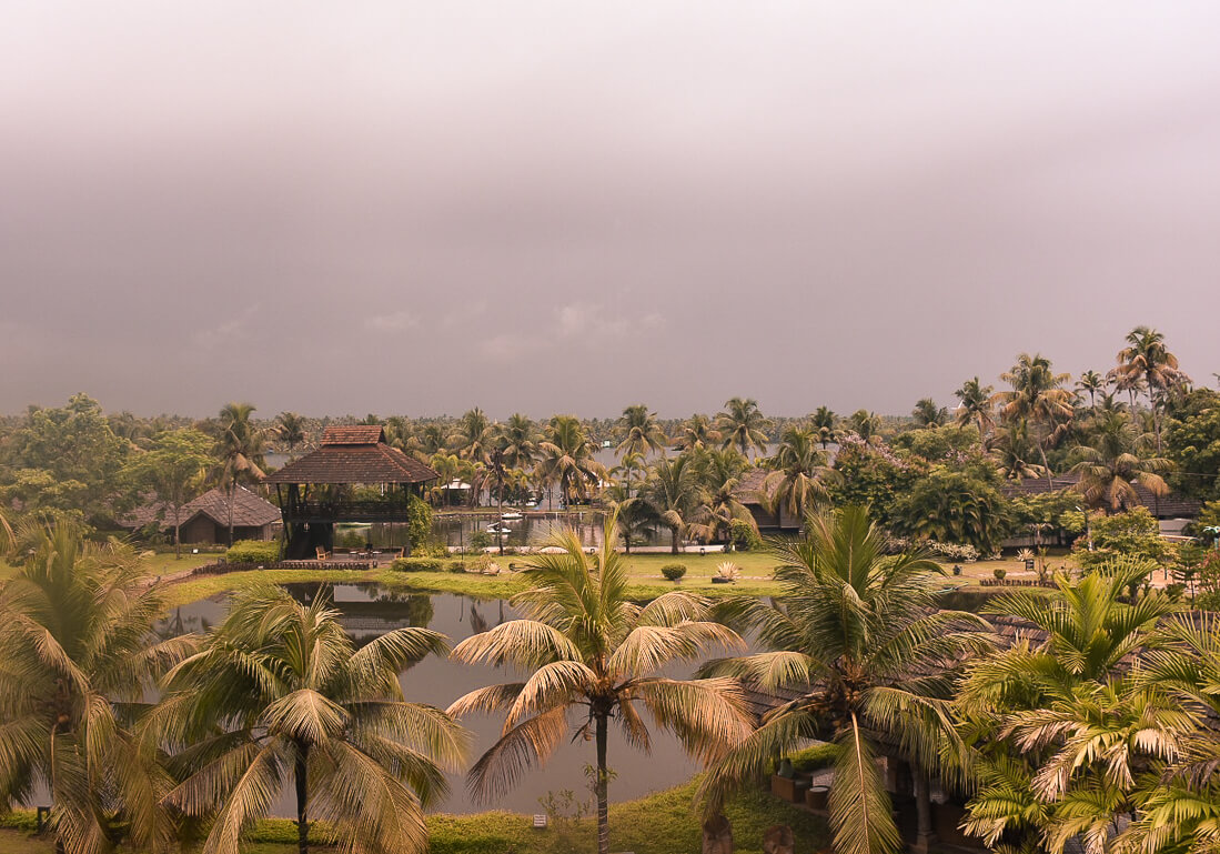 Looking over palm trees and Vembanad lake with dark storm clouds