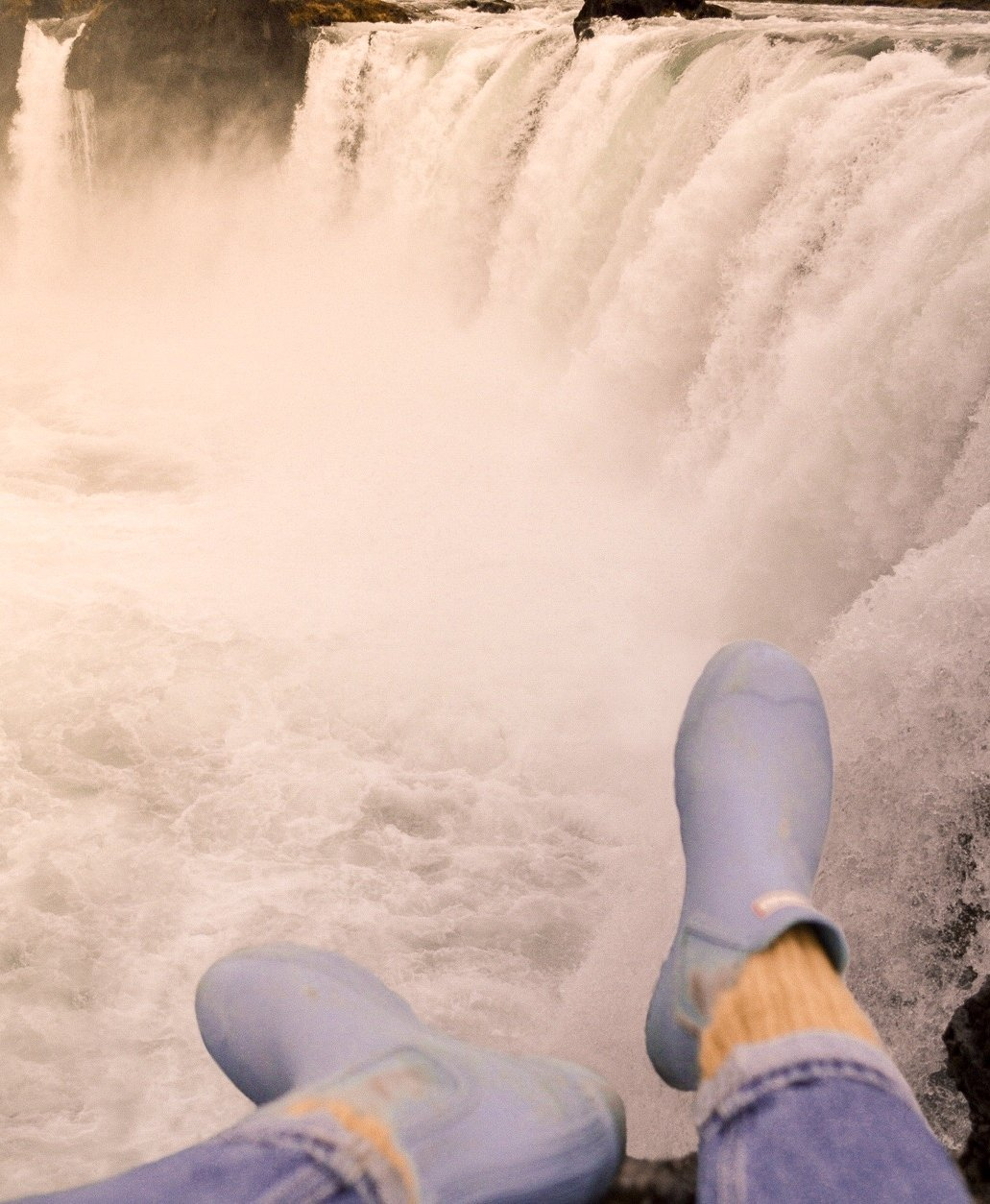 Blue Hunter boots hanging over the edge of Godafoss (a waterfall in Iceland)