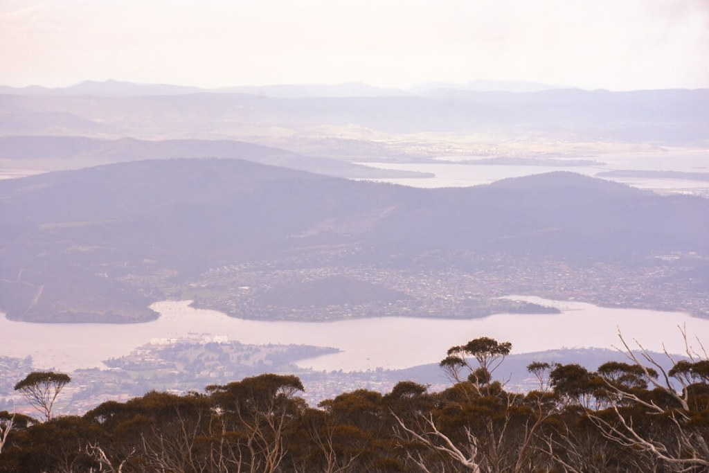 Looking down at Hobart (bays, inlets, cities and bushland) from high up a mountain