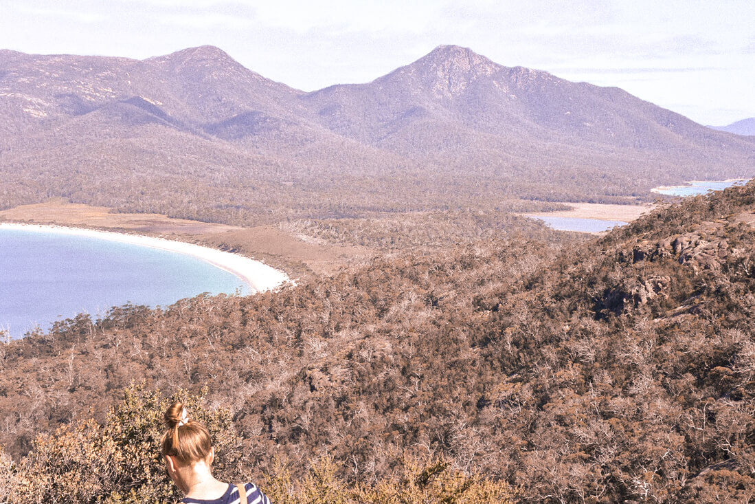 Girl with red hair in front of wineglass bay (white sandy beach shaped like wineglass with mountains behind)