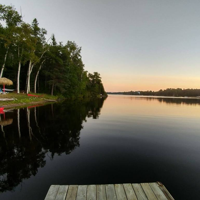 The picture shows Oxtongue lake at sunset. The lake looks almost black in this light