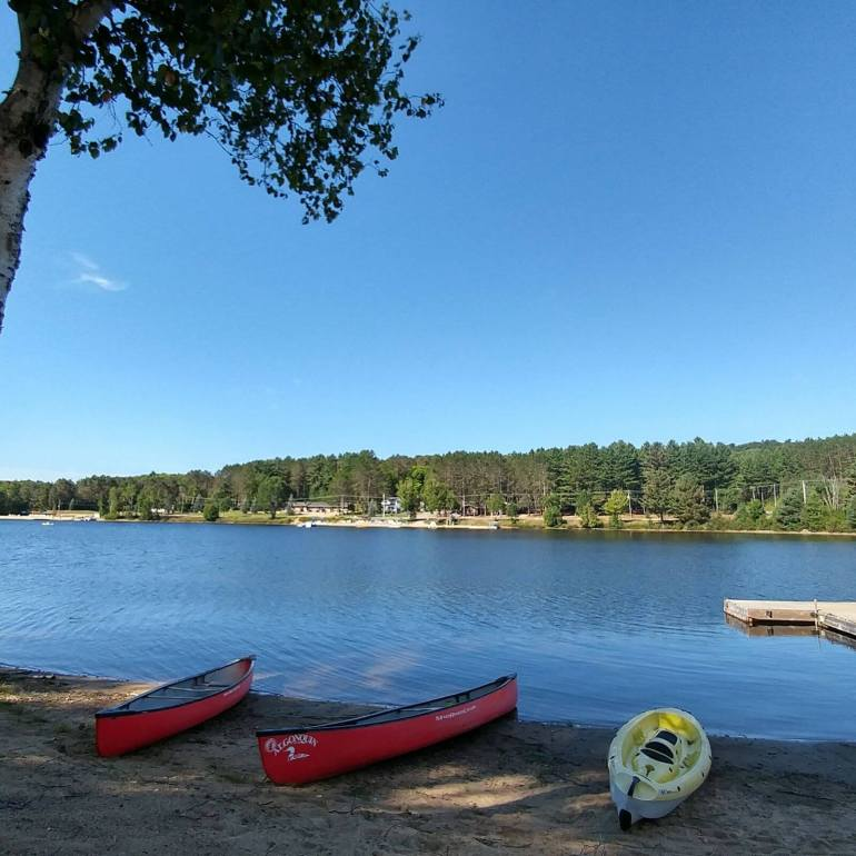 The picture shows three canoes, two red and one yellow , on the lakeshore of Oxtongue lake
