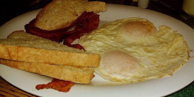 Ottumwa Iowa Hotels eggs, bacon, and toast on a plate.