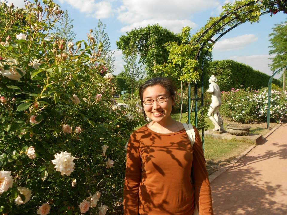 Author pictured with flowers in the Jardin des Plantes in Paris