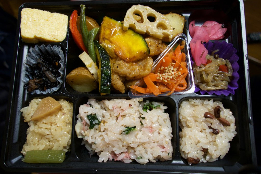 bento box including sticky rice, chicken and pickled radish and things.