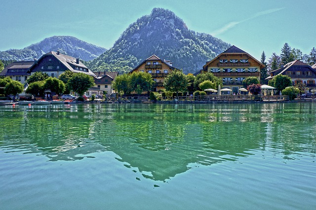 lago con riflesso di case affacciate di fronte con alberi e montagne