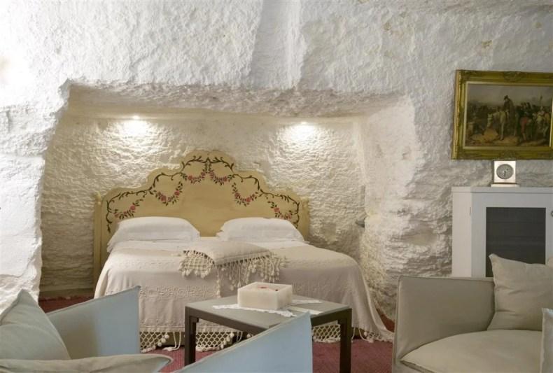 camera di colore bianco fatta di roccia con letto bianco d'epoca e piccoli divani