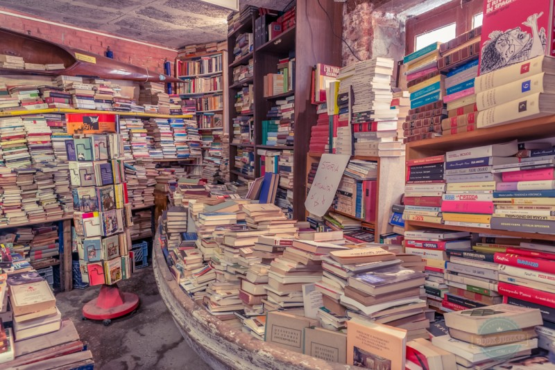 Libreria Acqua Alta Stacks of books in Boat in Venice Italy. This is to help prevent damage during acqua alta which happens each winter in this sinking city.