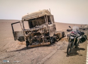 Burnt out truck on the side of the road in the middle of the Lut desert.