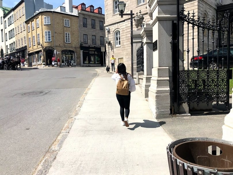 girl in white shirt and black pants walking in Quebec City, Canada