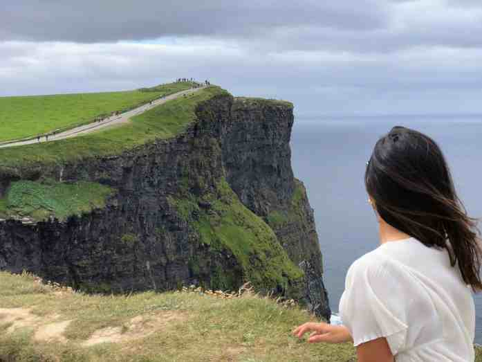 girl with brown hair looking at the cliffs of moher in ireland