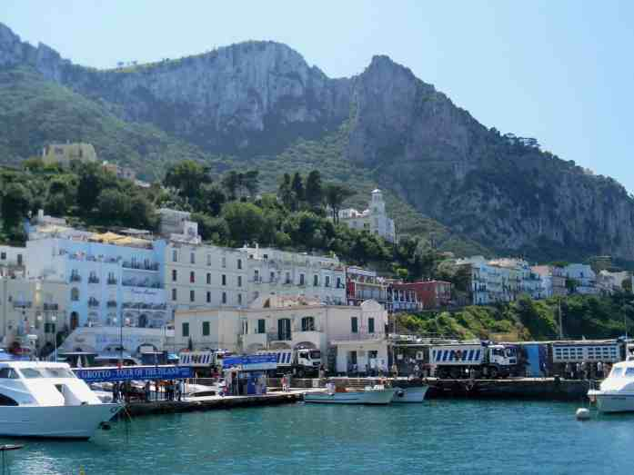 beachside town in italy, pastel colored buildings, mountains, the sea and boats