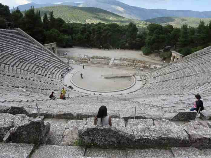 Girl sitting in an ancient Greek theater looking at the mountains