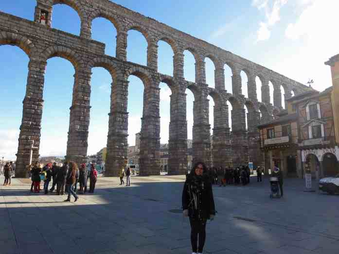 Girl with black coat smiling in front of roman aqueducts in Spain