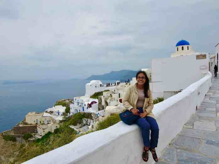 girl sitting on a white wall in Santorini Greece tapping into the feeling of travel