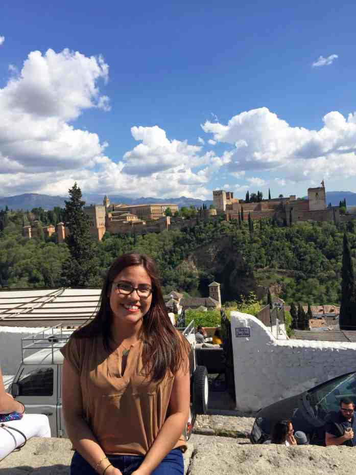 Happy girl with brown top and blue jeans and brown hair sitting with the Alhambra in the background in Granada. Blue skies.