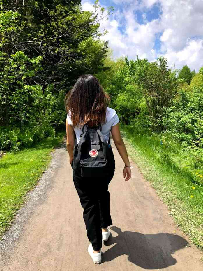 girl walking with a small black backpack outdoors