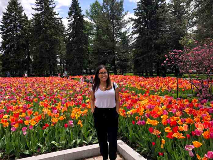 girl standing in front of a field of red and orange tulips