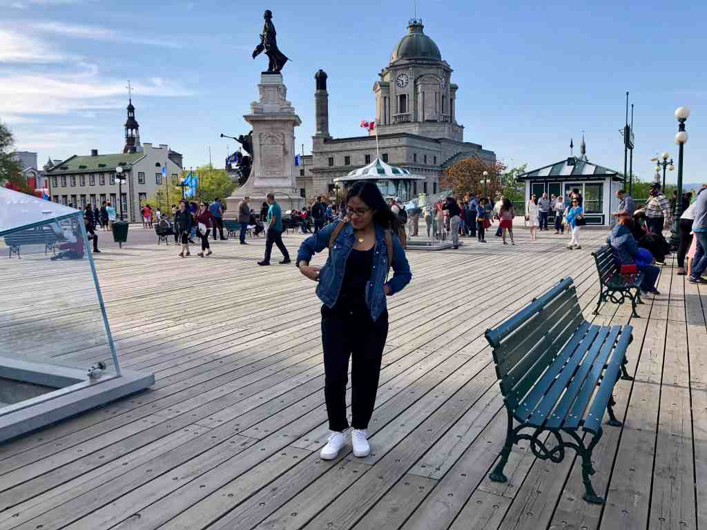girl with jean jacket, black pants and white shoes standing on boardwalk in quebec city, canada