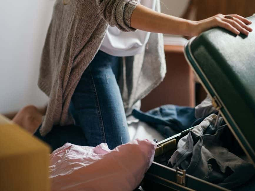 focused woman packing suitcase in bedroom