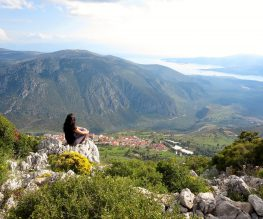 girl with black hair sitting on a green mountain