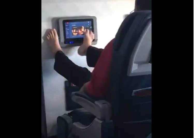 Paasenger Uses Feet on Airplane TV