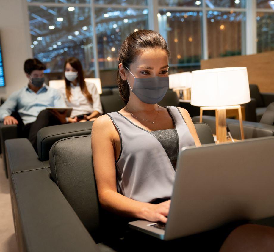 Traveler in VIP lounge working wearing mask