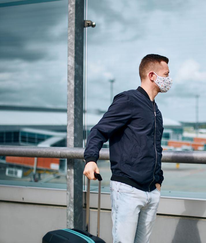 Traveler wearing mask with luggage