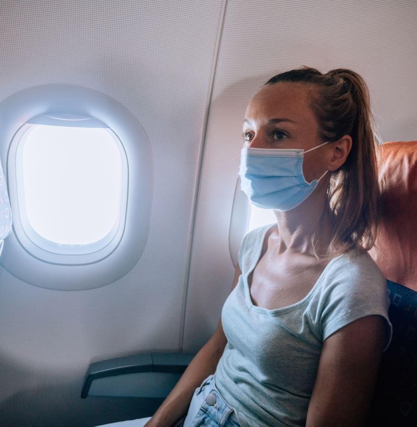 Female traveler in mask on plane