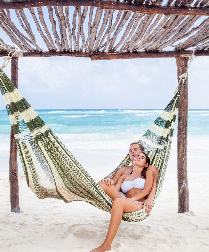 cancun couple laying in hammock on beach