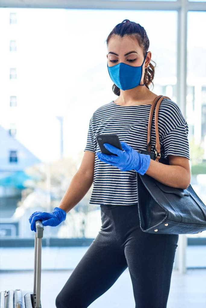 woman waits for flight in mask and gloves