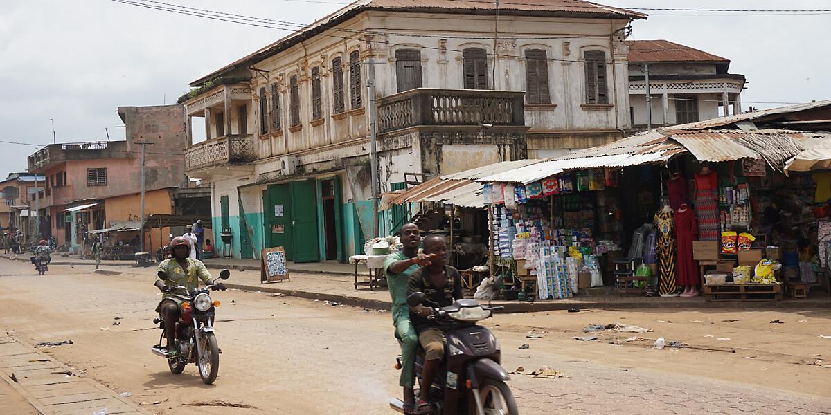 Alltagsleben vor kolonialer Architektur in Porto Novo, Benins Hauptstadt