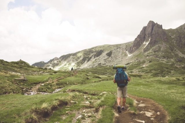 Male hiker in the mountains. View from back.