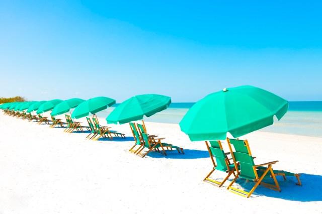 Green beach loungers and umbrellas at white sandy beach