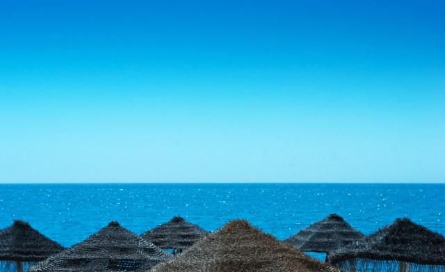 Clear blue sky above beach parasols
