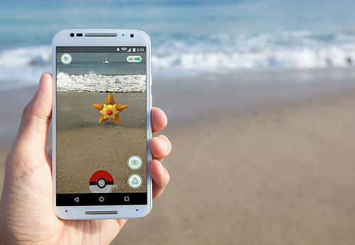Someone playing Pokemon Go on the beach