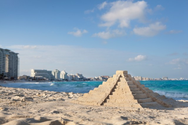 """Elaborate Chichen Itza pyramid sandcastle built with white sand of a Caribbean Sea beach, with Cancun, Mexico tourist hotel district buildings in the background. It resembles the main Temple of Kukulkan, or """"El Castillo"""" edifice in the historical pre-Columbian ruin, one of the official New Seven Wonders of the World."""