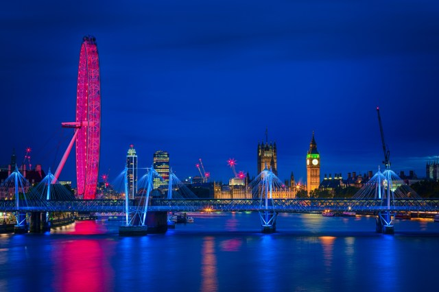 London panorama of Millenium wheel, Big Ben with the Houses of Parliament and Hungerford and Golden Jubilee bridges over river Thames at dusk.