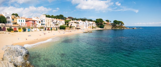 Holidaymakers relaxing on the idyllic Platja de Canadell, one of Calella de Palafrugell's beaches on the Costa Brava in Catalonia, Spain.