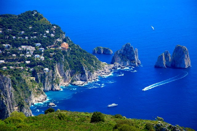 Above Capri Island boats and Faraglioni - Blue mediterranean, Italy