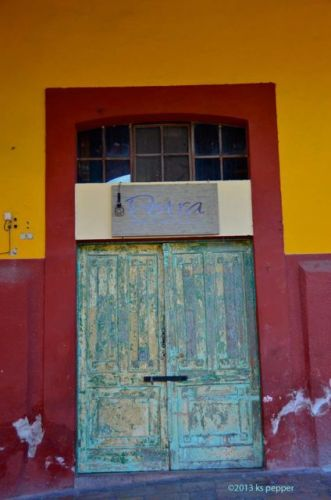 Distressed door on red and yellow wall