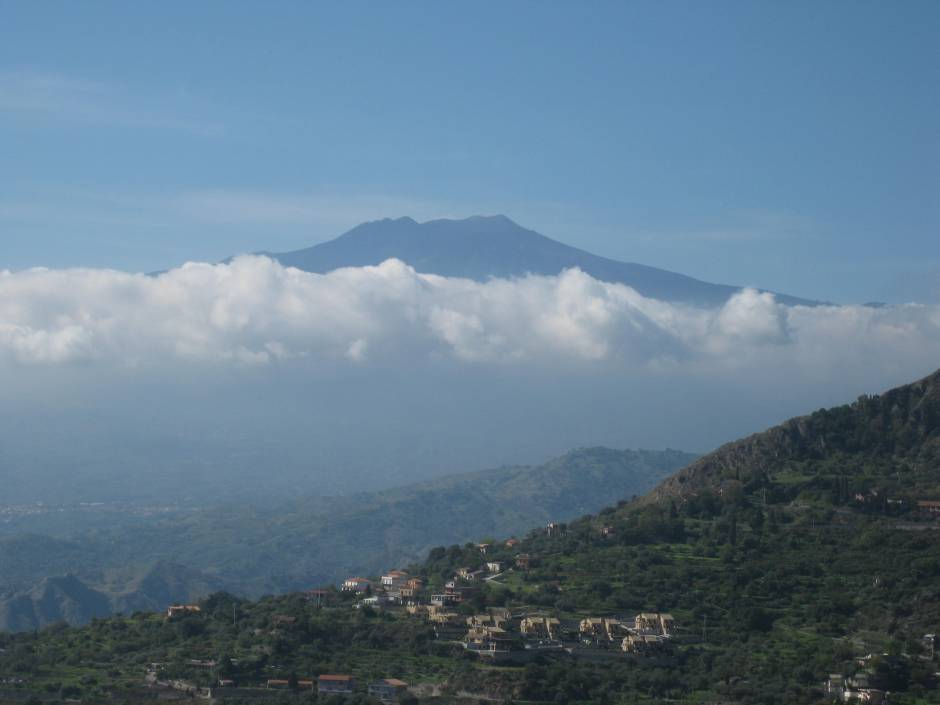 Mt. Etna peaks through the clouds, Taormina, Sicily.