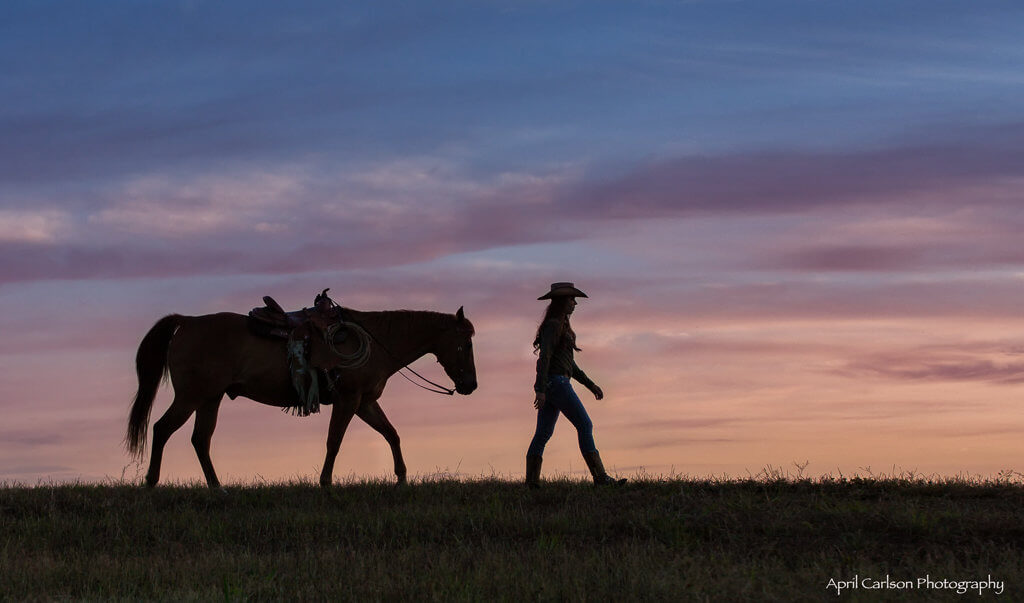 Horse Photography Workshop: Silhouette of cowgirl and her horse walking across the ridge at sunset