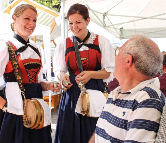 A tourist share a laugh with schnapps servers from Rinn.